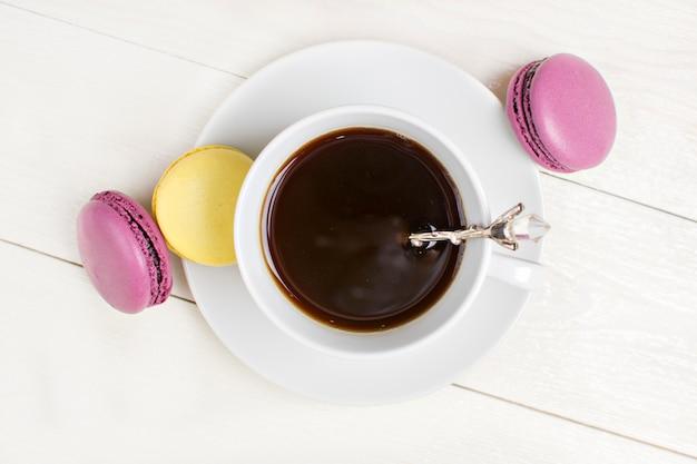 Tasse kaffee mit macaron auf weißem hölzernem hintergrund. flach legen