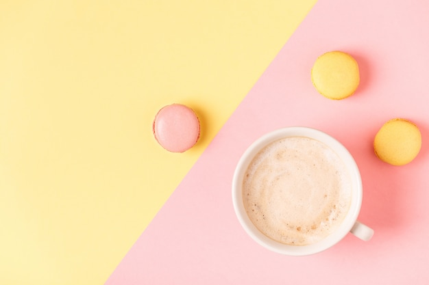 Tasse kaffee mit makronen auf pastellhintergrund