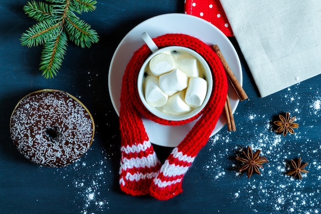 Tasse kaffee mit marshmallows, donut, zimt und sternanis.