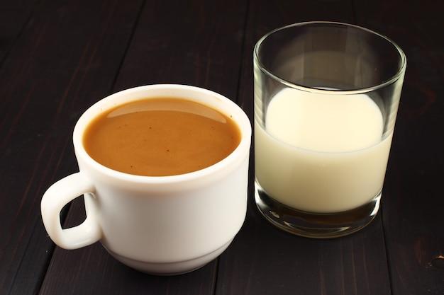 Tasse kaffee mit milch auf einer dunklen oberfläche