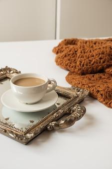 Tasse kaffee mit milch auf vintage goldenes tablett und gestrickte braune decke plaid auf weißem hintergrund