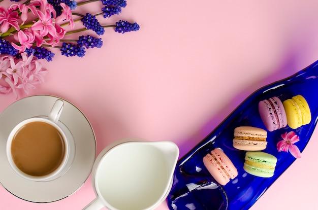 Tasse kaffee mit milch, macarons, milchglas auf pastell pinkept. kopieren sie platz