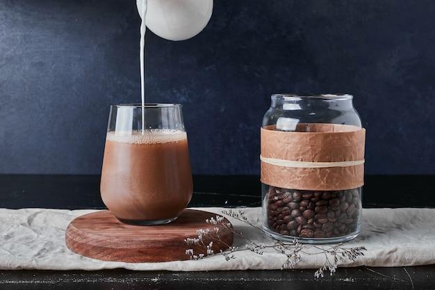Tasse kaffee mit milch und bohnen.