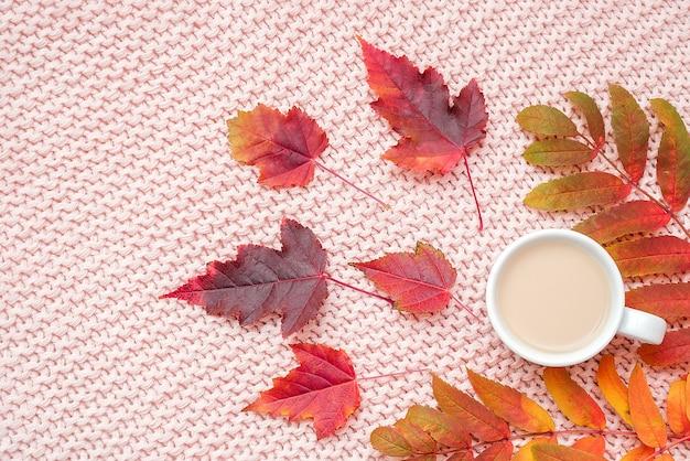 Tasse kaffee mit milch und buntem herbstlaub auf pastellrosa strickte plaidhintergrund. herbst gemütlich.