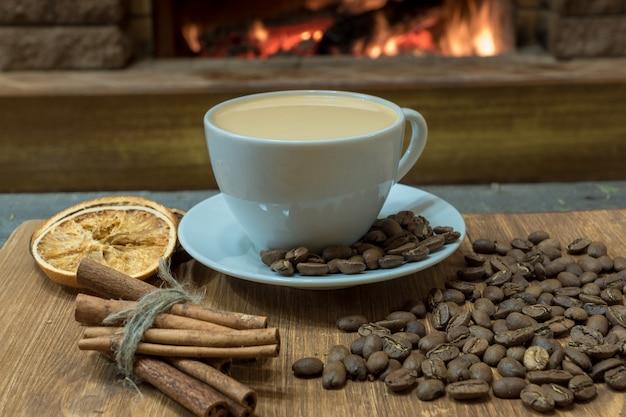 Tasse kaffee mit milch und kaffeebohnen um die tasse, zimtstangen, orange kandierte früchte.