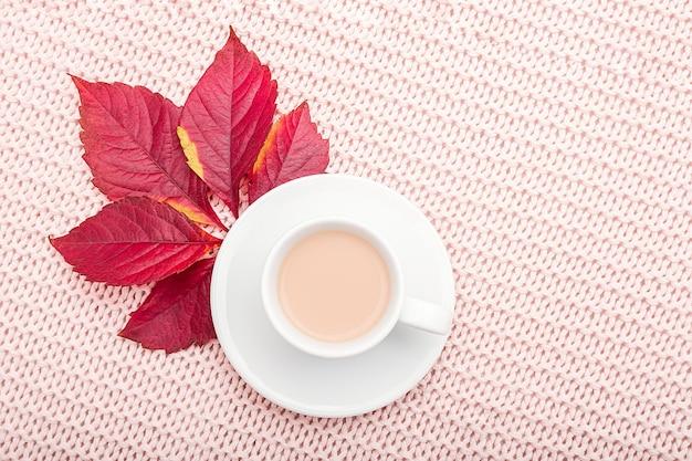 Tasse kaffee mit milch und rotem herbstlaub auf pastellrosa gestricktem plaidhintergrund.