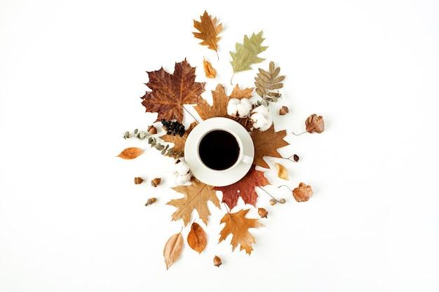 Tasse kaffee mit milch, wattestäbchen, eicheln, trockenen blättern auf weiß. flache lage, draufsicht