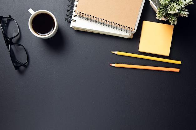 Tasse kaffee mit notizblock und stiften mit papier auf tisch