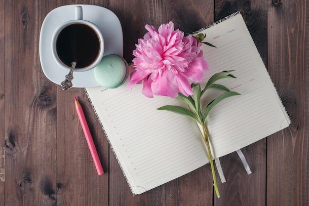 Tasse kaffee mit notizbuch auf dem hölzernen hintergrund