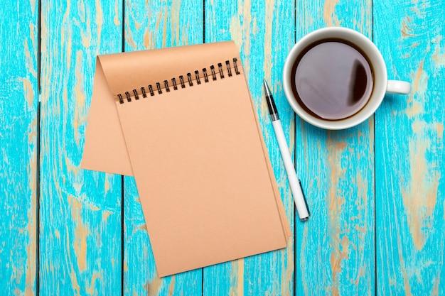 Tasse kaffee mit notizbuch auf hölzernem schreibtisch