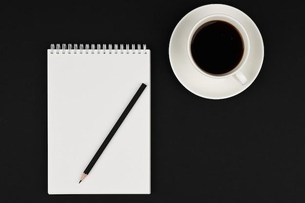 Tasse kaffee mit notizbuch und schwarzem bleistift auf schwarzraum. geschäftsplaner