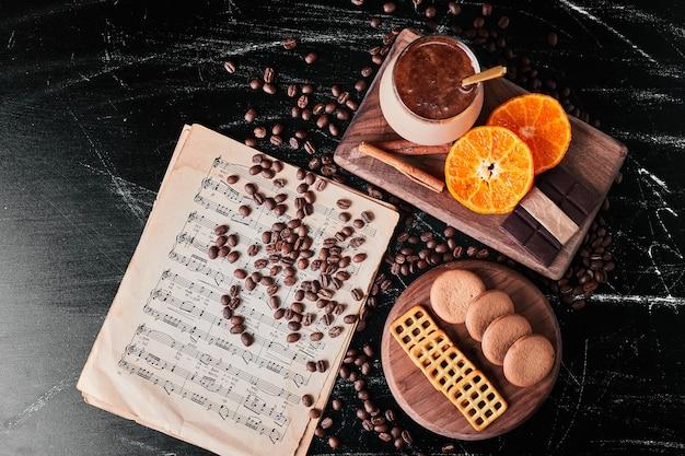 Tasse kaffee mit orangenscheiben und keksen.