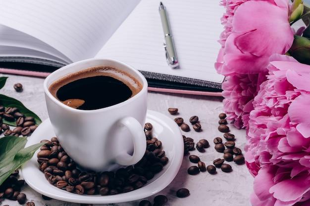 Tasse kaffee mit pfingstrosen auf dem tisch