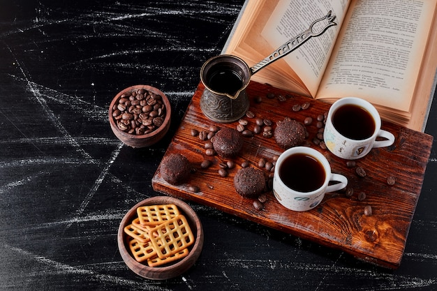 Tasse kaffee mit pralinen und keksen.