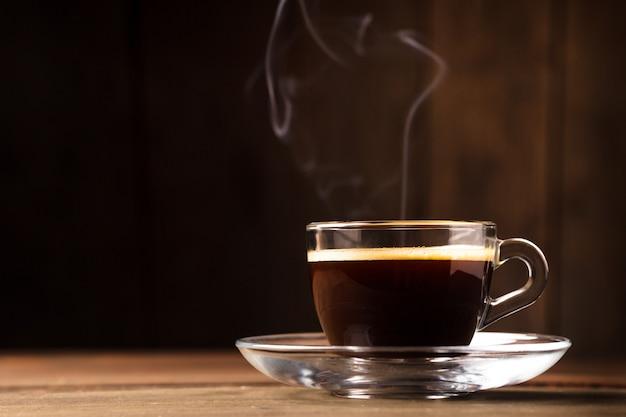Tasse kaffee mit rauch auf dem hölzernen hintergrund