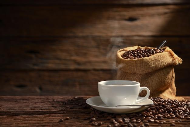 Tasse kaffee mit rauch und kaffeebohnen auf altem hölzernem hintergrund