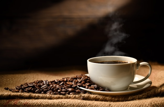 Tasse kaffee mit rauch und kaffeebohnen auf leinensack auf altem hölzernem hintergrund