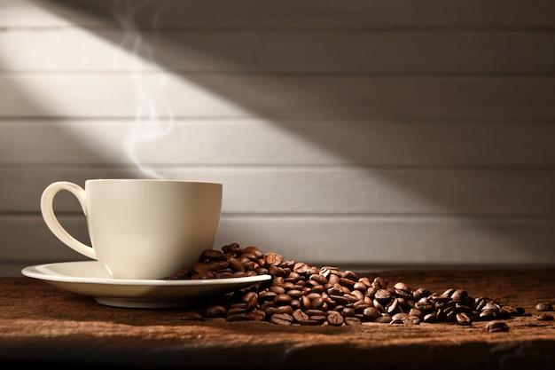 Tasse kaffee mit rauche und kaffeebohnen auf hölzernem hintergrund