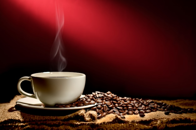 Tasse kaffee mit rauche und kaffeebohnen auf rotbraunem hintergrund