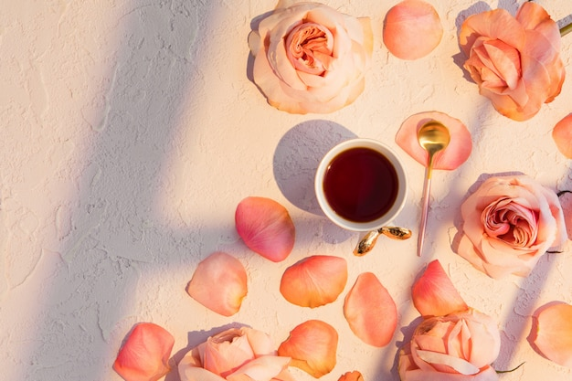 Tasse kaffee mit rosa rosenblumen und -blumenblättern.