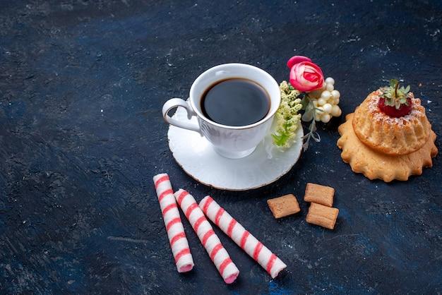 Tasse kaffee mit rosa stockbonbons und kuchen auf blauem, süßem keks-kaffeegetränk