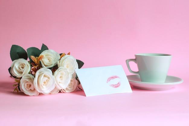 Tasse kaffee mit rose und kuss auf weißem umschlag lokalisiert auf rosa hintergrund