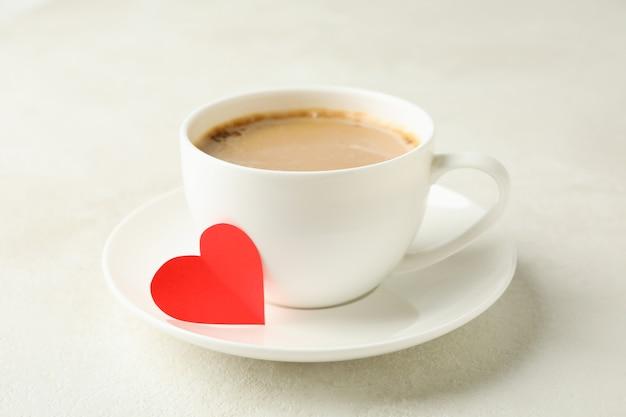 Tasse kaffee mit rotem herzen auf weißem strukturiertem tisch
