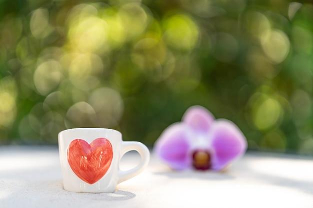 Tasse kaffee mit rotem herzen gedruckt auf sand gegen weichzeichnerblumenhintergrund.