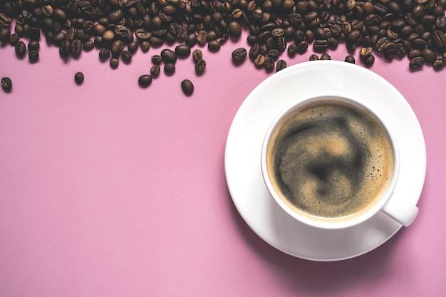 Tasse kaffee mit schaum und bohnen auf rosa hintergrund.
