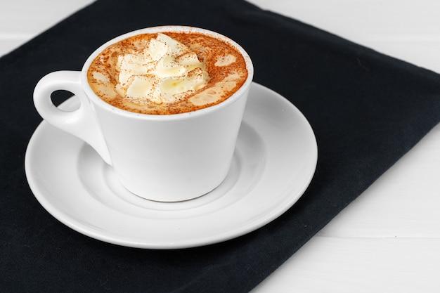 Tasse kaffee mit schlagsahne auf weißem tisch nah oben