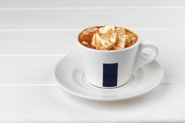 Tasse kaffee mit schlagsahne auf weißem tisch
