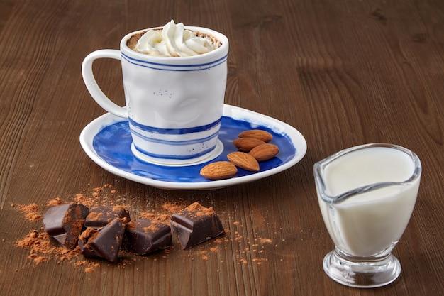 Tasse kaffee mit schlagsahne und mandeln