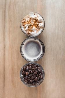 Tasse kaffee mit schlagsahne und röstkaffeebohnen auf hölzernem hintergrund