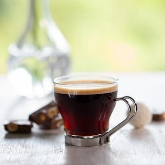 Tasse kaffee mit schokolade auf weißem holztisch