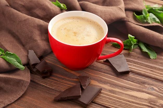 Tasse kaffee mit schokoladenstücken auf dem tisch