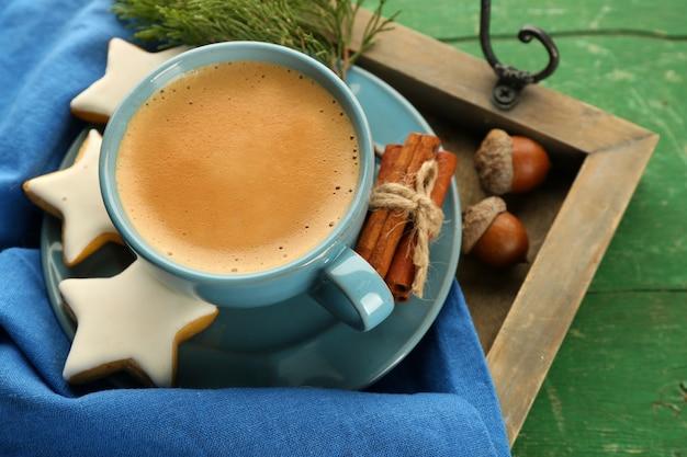Tasse kaffee mit sternförmigen keksen auf serviette auf holztablett