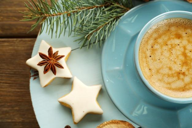 Tasse kaffee mit sternförmigen keksen und weihnachtsbaumast auf holzmatte
