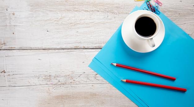 Tasse kaffee mit stiften auf blauem papier auf tisch