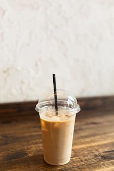 Tasse kaffee mit stroh auf dem boden
