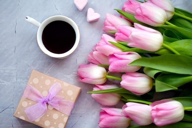 Tasse kaffee mit süßigkeiten und tulpen. geschenk für mama. konzept des frühlings. feierlicher hintergrund. blumen mit kaffee und süßigkeiten. frühstück mit blumen.