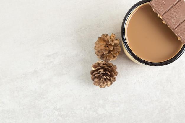 Tasse kaffee mit tannenzapfen und schokoriegel.