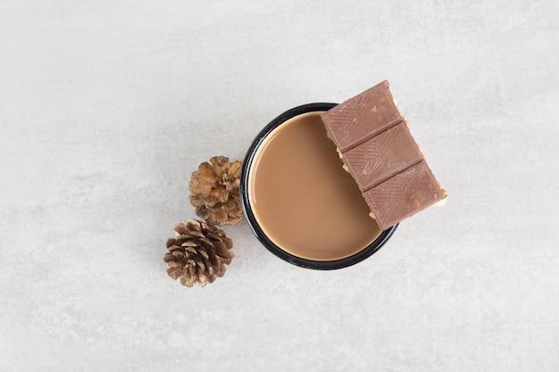 Tasse kaffee mit tannenzapfen und schokoriegel