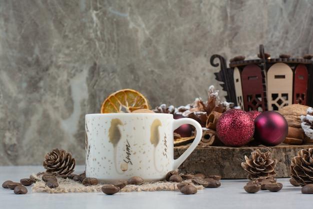 Tasse kaffee mit tannenzapfen und weihnachtskugeln auf holzteller. hochwertiges foto