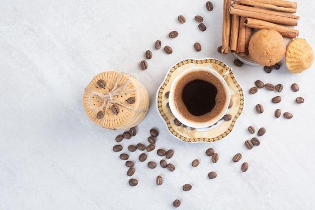 Tasse kaffee mit verschiedenen keksen und kaffeebohnen