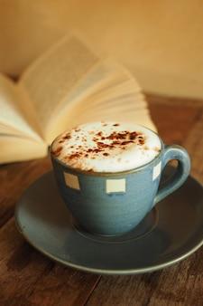 Tasse kaffee mit viel schaum und ein buch hinter