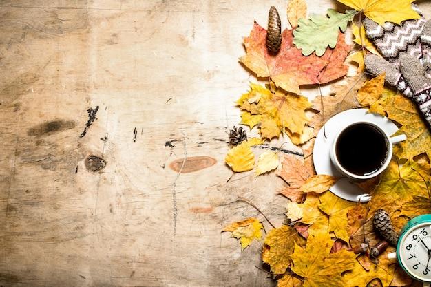 Tasse kaffee mit wecker auf herbstlaub