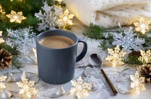 Tasse kaffee mit weihnachtsdekorationen auf holztisch. warme gemütliche atmosphäre. weicher fokus.