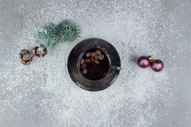 Tasse kaffee mit weihnachtsdekorationen auf kokosnusspulver auf marmor