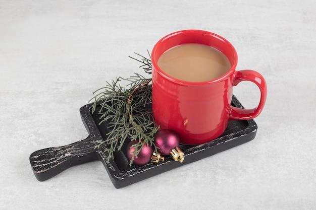 Tasse kaffee mit weihnachtsschmuck auf dunklem brett