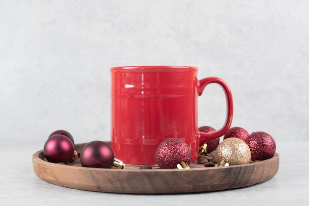 Tasse kaffee mit weihnachtsschmuck auf holzteller